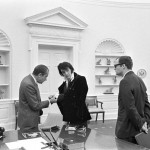 Nixon is admiring the cuff links given to Elvis by Vice-President, Spiro Agnew.